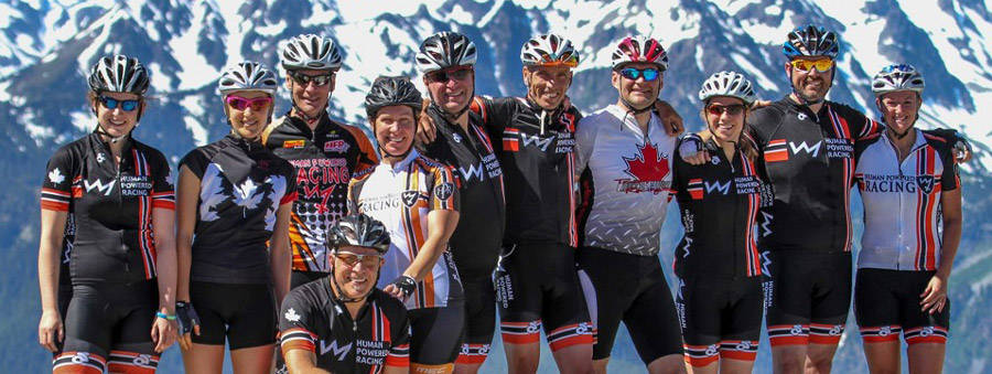 The Human Powered Racing Team stands triumphant, with sunglasses, in front of mountains.