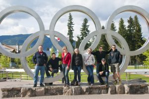 Group shot of athletes and coach in the Olympic rings at Whistler Village