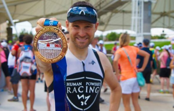 Adrian holding up his finishing medal from the 70.3 World Championship in Las Vegas