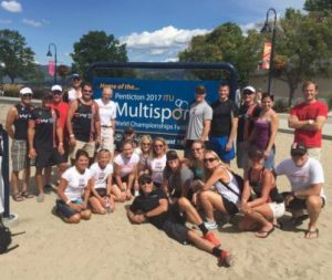 Human Powered Racing Team on the beach in front of the ITU Mutlispor sign in Penticton BC.