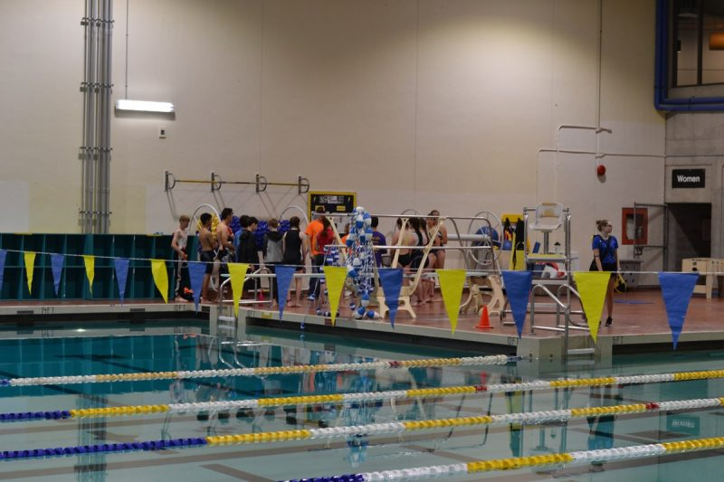 Athletes huddle on the pool deck right before the race.