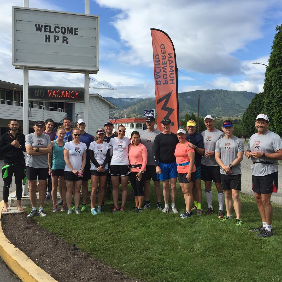 "Underneath a tall sign that says ""Welcome HPR"" is a large group of people in running gear who are smiling. Just behind them there is also a tall orange flag that says ""Human Powered Racing"" with the HPR logo, which is a black line that looks like the silhouette of a mountain range. There are mountains and a blue sky in the background."