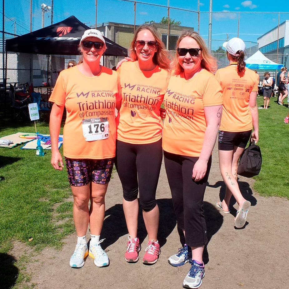 "Three women standing shoulder to shoulder with their arms around each other. There are wearing matching orange shirts that say ""Human Powered Racing Triathlon of Compassion"" and are standing on a grassy green field."