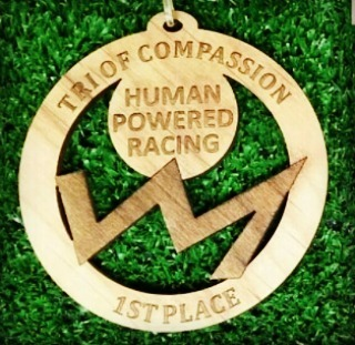 "A wooden medal lying on green grass. It says ""Tri of Compassion"" at the top, ""1st Place"" at the bottom, and ""Human Powered Racing,"" in the middle above their logo, which looks like the silhouette of a jagged mountain range."