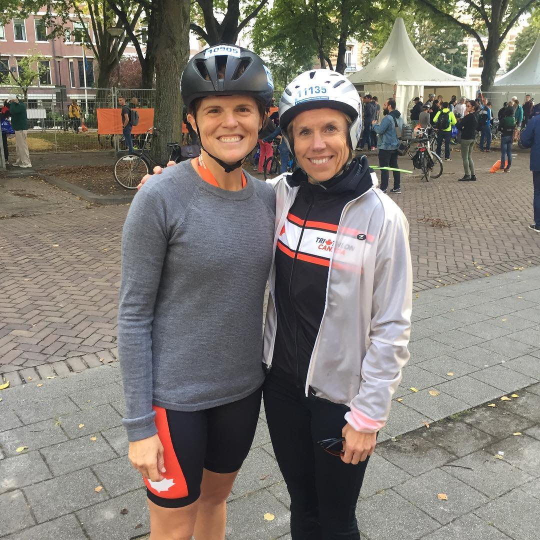 Photo of two women standing on a brick sidewalk with their arms around each other. Both have helmets and both are smiling. It is daylight.