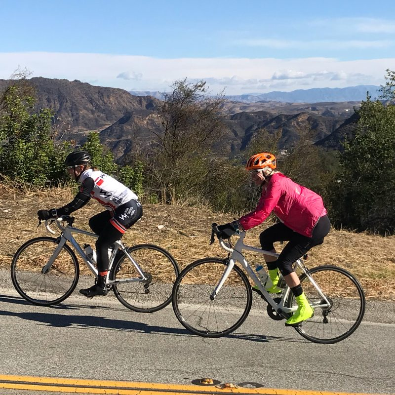 This is a photo of two women on bikes going up hill on the road. Behind them is a landscape of dry grass, trees, and low mountains