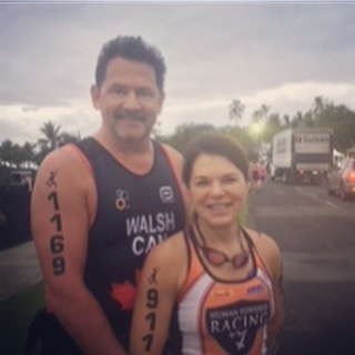 A man and woman standing outside on a grey day with palm trees in the background. Both are smiling, and wearing triathlon tank tops. We only see down to their waists, and the man is standing behind the woman. They are angled slightly to face more towards the right.