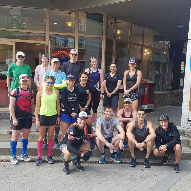 This is a group photo of people in running gear standgin outside of a class building with wooden frames for the floor to ceiling windows. They are outside but you cannot see the sky because of the building behind them.