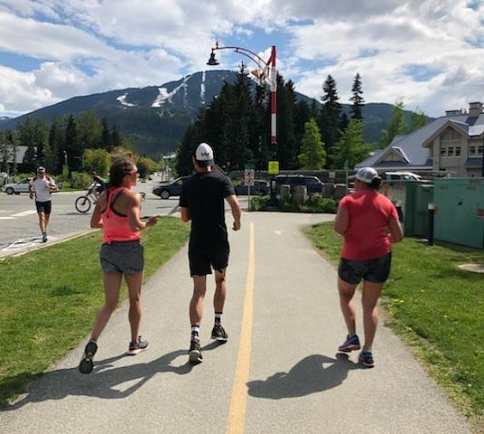 This is a photo of two women running in blood orange shirts with a man in a black tshirt running in the middle. They are running along a wide sidewalk away from the camera and towards a background of a large, snowy mountain and evergreen trees.