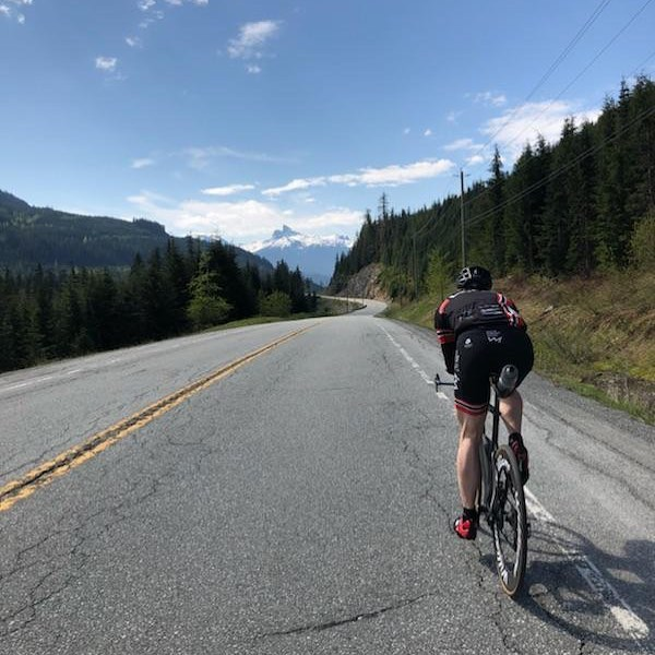 This is a photo of a long flat road with evergreen trees on either side and a mountain at the end. It is a sunny, clear day and a biker is going away from the camera towards the mountain on the right side of the road.