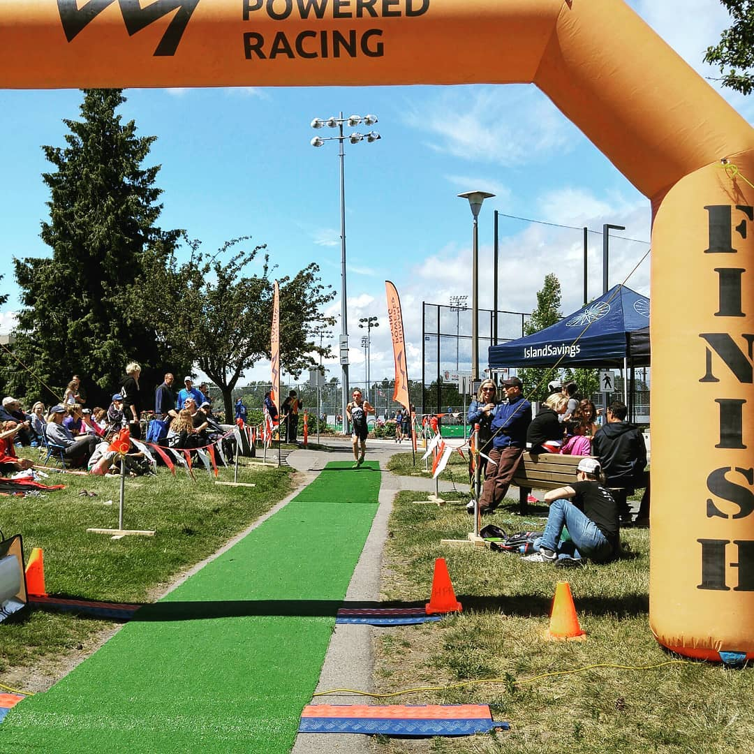 An inflatable orange archway the says 'finish' on the right side. There is a long false grass aisle with a racer in the distance running along it towards the finish line.