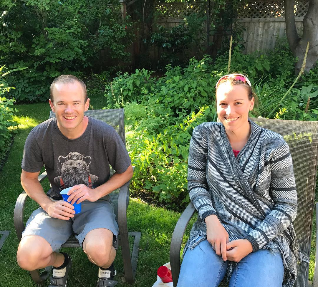 A man on the left and a woman on the right sitting outside in a yard and smiling. It is sunny and the grass and shrubbery behind them is bright green. The man is holding a plastic cup.