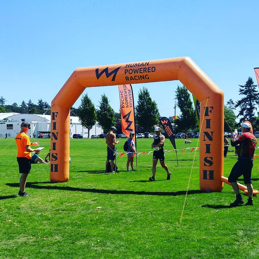 """An orange inflatable archway finish and start line marker that says """"Human Powered Racing"""" on it with their logo, which is a jagged line shaped like a mountain range silhouette. There is a man in an orange tshirt on one side with the clipboard, and man in a black triathlon bodysuit walking through and others milling about around it. It is on a green grass field with a clear blue sky and trees in the background."""