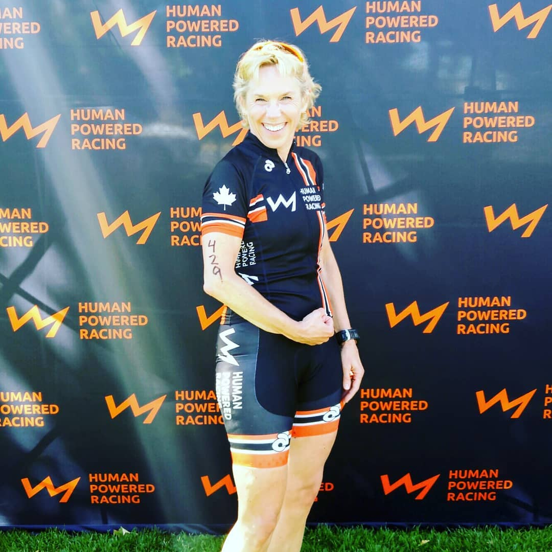 A woman with short blonde hair is wearing an HPR triathlon bodysuit and flexing her right arm. She is smiling and posing in front of the HPR back drop with their logo on it in orange, which is a line in the shape of a jagged mountain range silhouette.