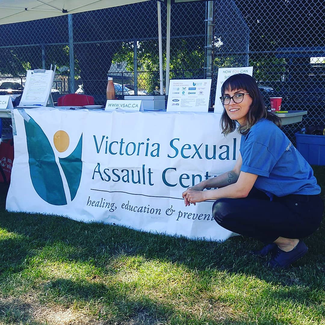 """A woman is kneeling to the right of a sign the is tied to a table and says """"Victoria Sexual Assault Centre."""" She has brown hair, glasses, and is smiling at the camera. She is wearing a blue tshirt and black pants."""