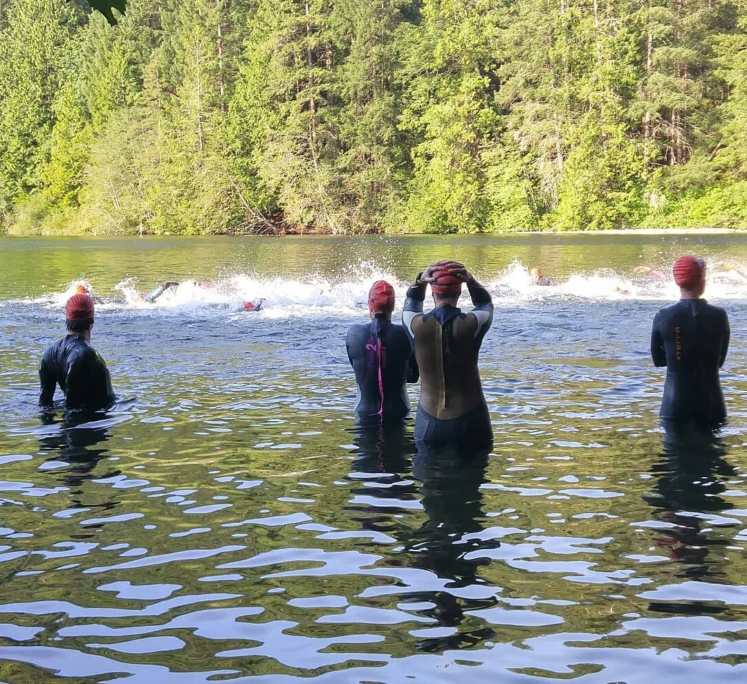 A group of people in wet suits getting into a lake. They are facing away from the camera. You can see evergreen trees on the far side of the lake.
