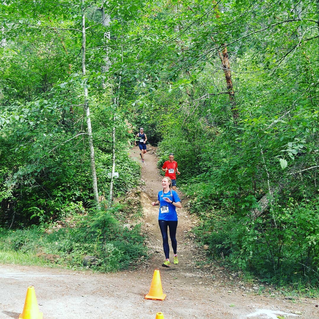 A woman in a blue shirt running down a hill on a trail with a man in a red shirt just behind her. They are surrounded by green trees and there are two yellow cones in the foreground.