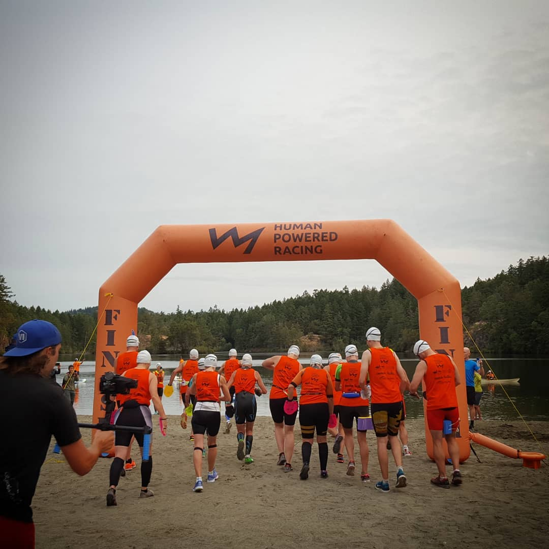 A group of people in matching orange tank tops, swim caps, and goggles seen from behind running through an inflatable orange Human Powered Racing Start and Finish line shaped like an arch way. They are on sand, there is a lake in front of them, and there are evergreen trees surrounding the lake. It is a grey day.