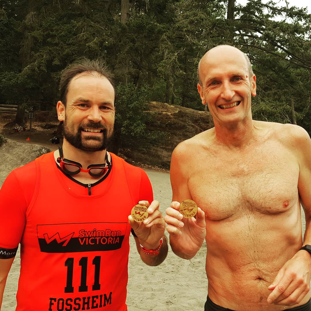 Two men standing shoulder to shoulder on a beach with evergreen trees in the back ground. Both are smiling and holding up wooden pendants or medals. The one on the left has a brown beard and orange tshirt. The one on the right is bald and shirtless. We see them from the waist up.