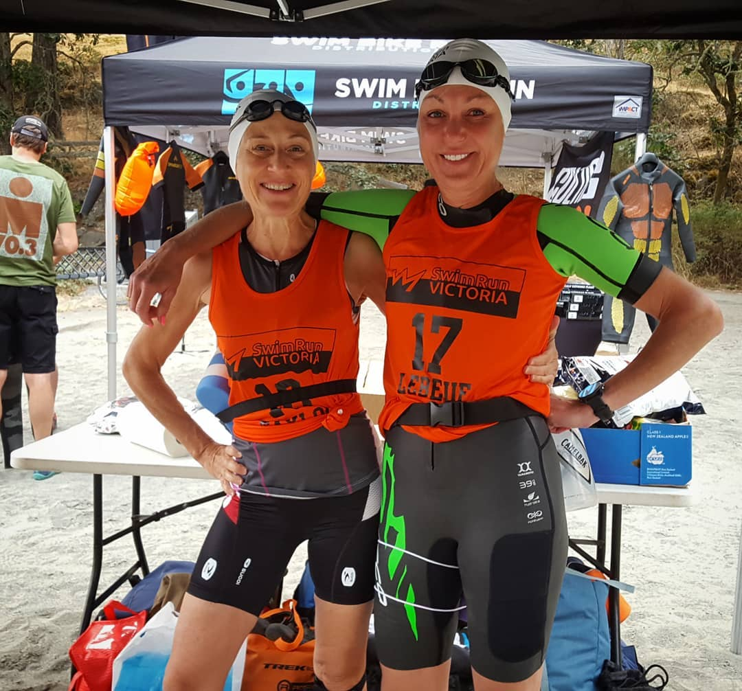 Two women in matching orange SwimRun Victoria tank tops. They are also wearing swim caps and goggles. They are standing on sand and there is a black tent in the background. There are some leafless trees in the background.