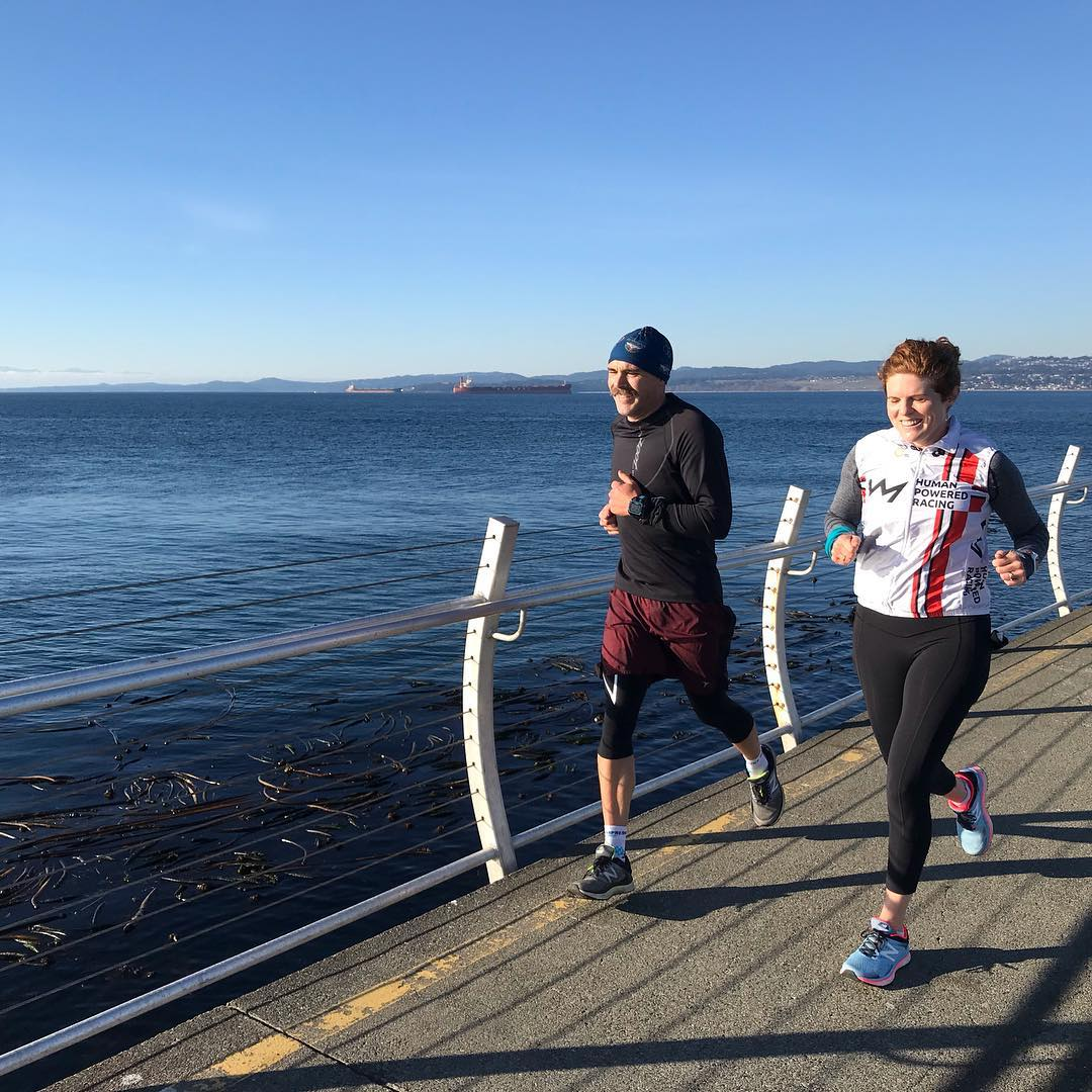A woman running on the right and a man running on the left. They are running along Ogden Point, which is a paved walkway out to a small lighthouse in Victoria. Past the curved metal fence there is blue ocean and mountains in the distance. It is a clear, sunny day.