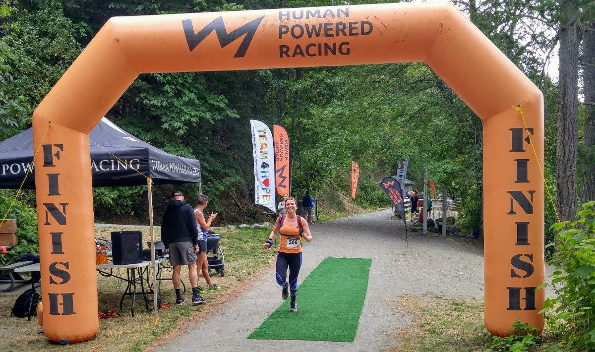 "Baylee wearing black tights and an orange top running through an orange inflatable finish line that reads ""Human Powered Racing"" on the top. She is running on a gravel road with green trees behind her. She is smiling widely."