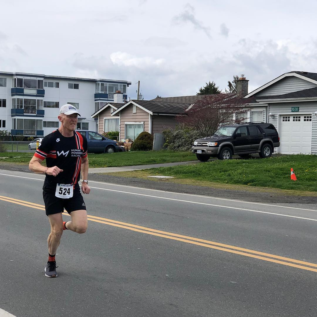 Rob in a black and red human powered racing shirt and black shorts running along a road.