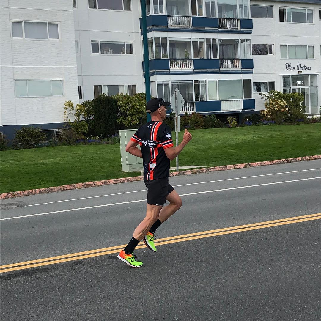 A man in a black and red human powered racing shirt and black shorts running along a road.