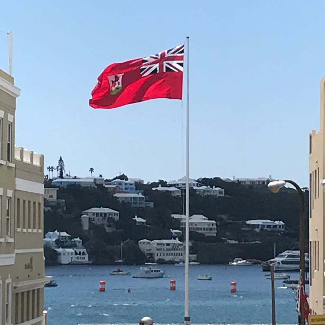 The red Bermuda flag flies in the centre between to white buildings with water behind it. The sky is clear and blue.
