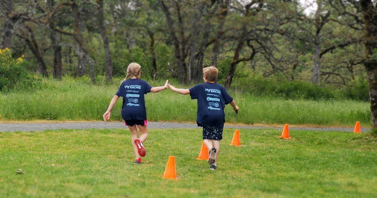 two kids high fiving as they run along at the Vic Youth Triathlon West Shore