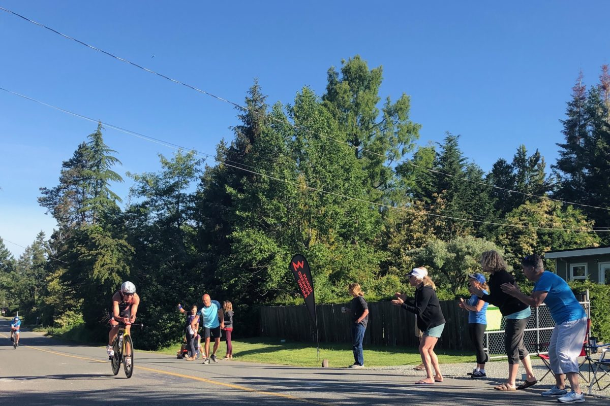 Mike Neill riding past HPR cheer station at Jay Kriegers house on bike at Victoria 70.3