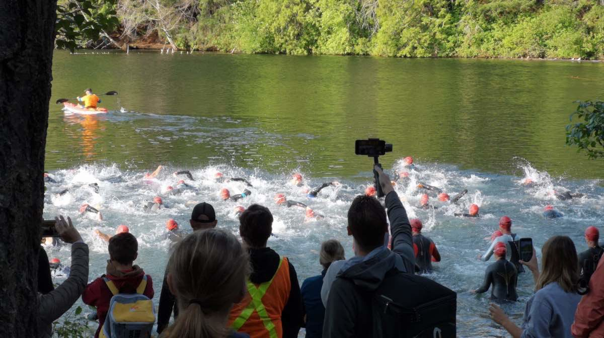 A crowd faces away from the camera towards a lake made turbulent by a crowd of racers starting the swim.