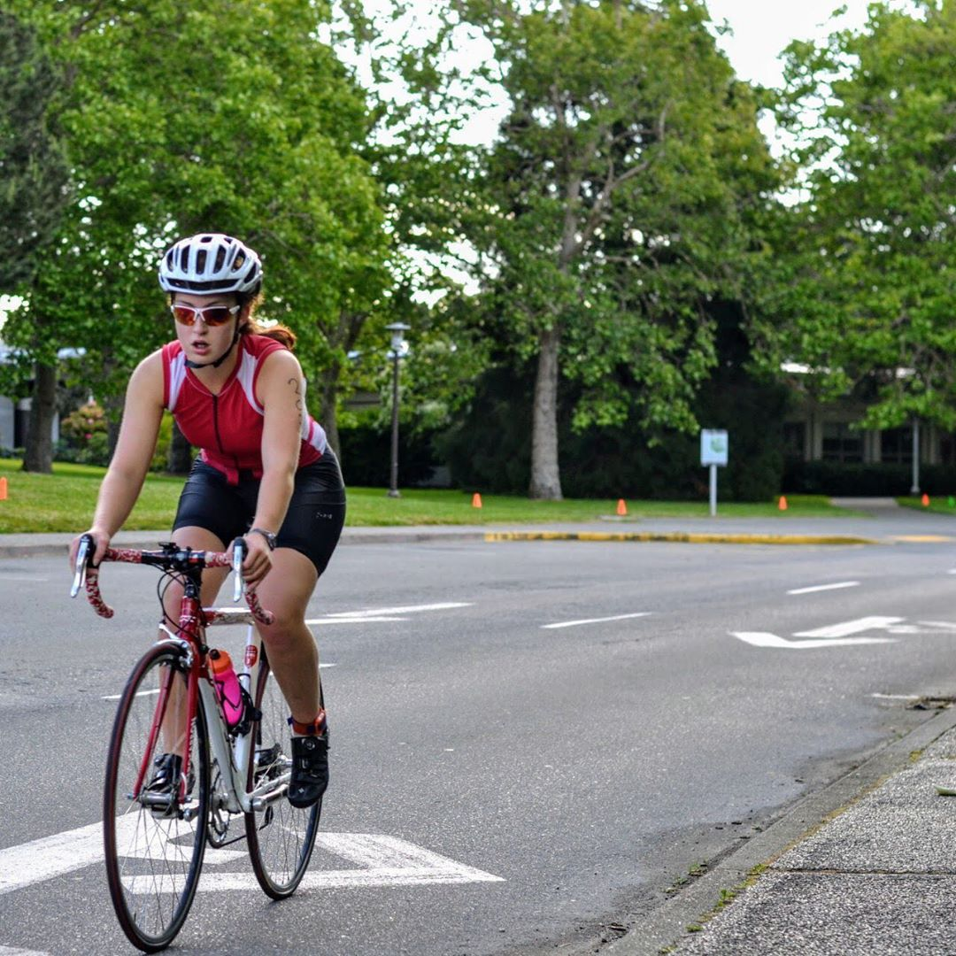 A young woman rides her bike towards the camera along ring road on the UVic campus.