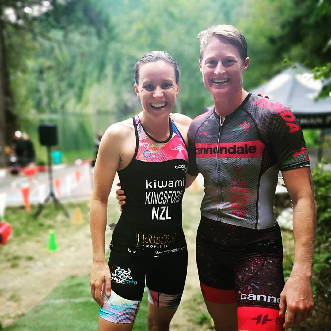 Two people standing side by side with their arms around each other muddy and smiling in their triathlon suits.