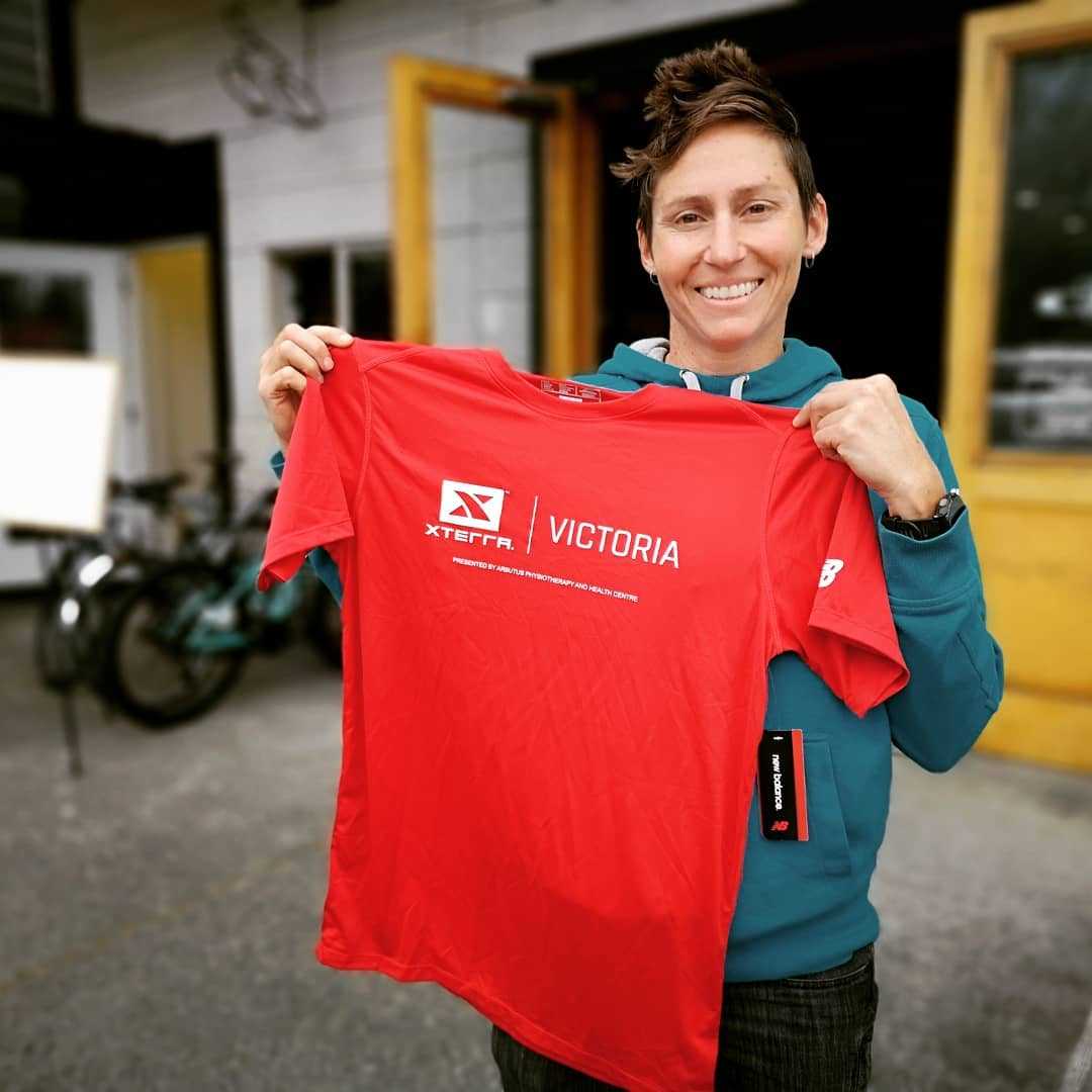 A woman holding up a red XTERRA tshirt and smiling outside of Trek Cycles.