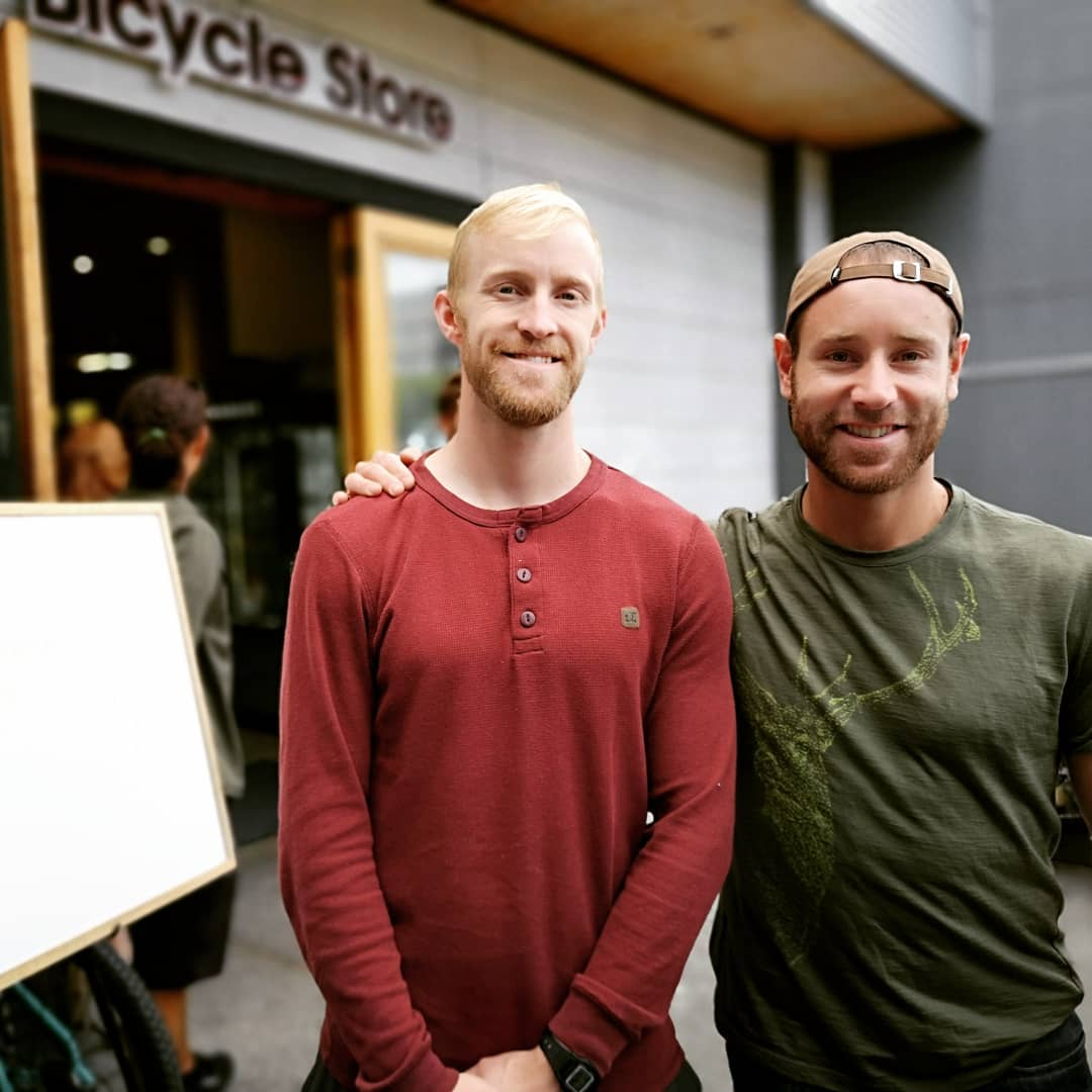 Two men standing shoulder to shoulder and smiling outside of Trek Cycles.