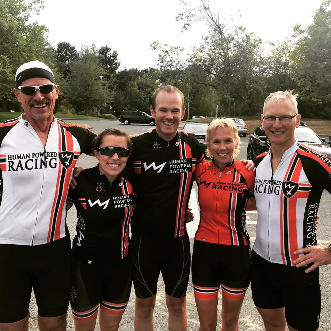 Five athletes in their human powered racing gear in a row with their arms around each other smiling.