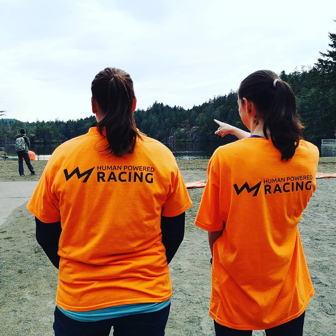 Two volunteers stand shoulder to hsoulder facing away from the camera to show the HPR logo on the backs of their orange tshirts.