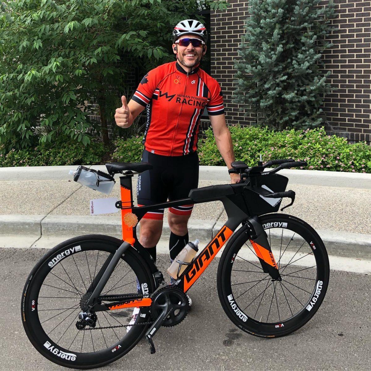 Chris Mavrikos athlete standing in front of his bike before Calgary 70.3