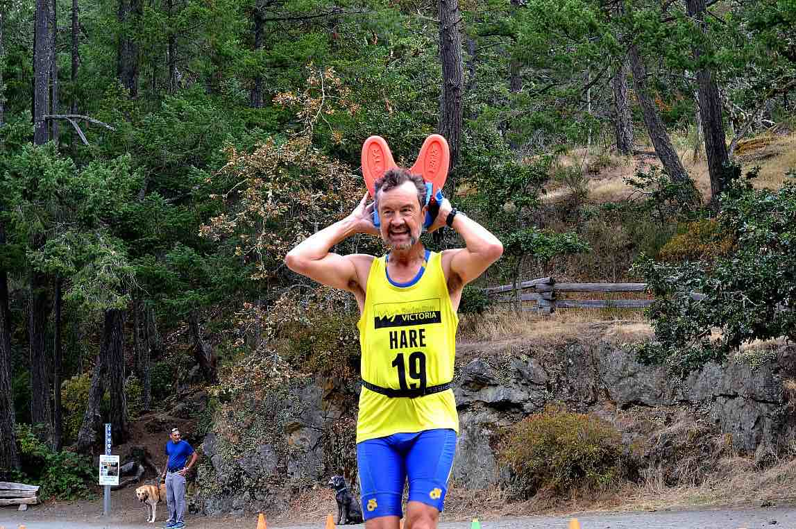 A man smiles widely crossing the finish line with flippers held behind his head like ears.