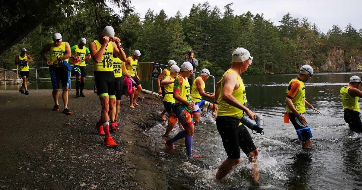 A large group of people in swim and run gear run into a lake.