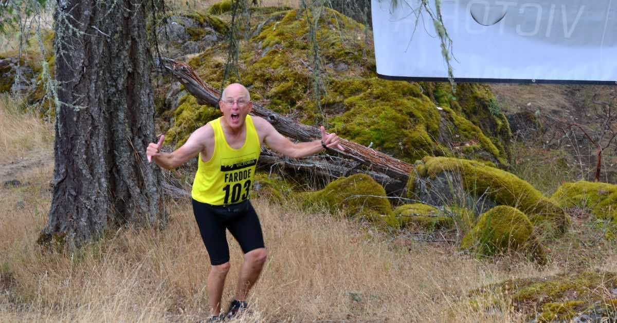 A man runs through tall dry grass in a forest making a thumbs up, mouth wide and smiling.