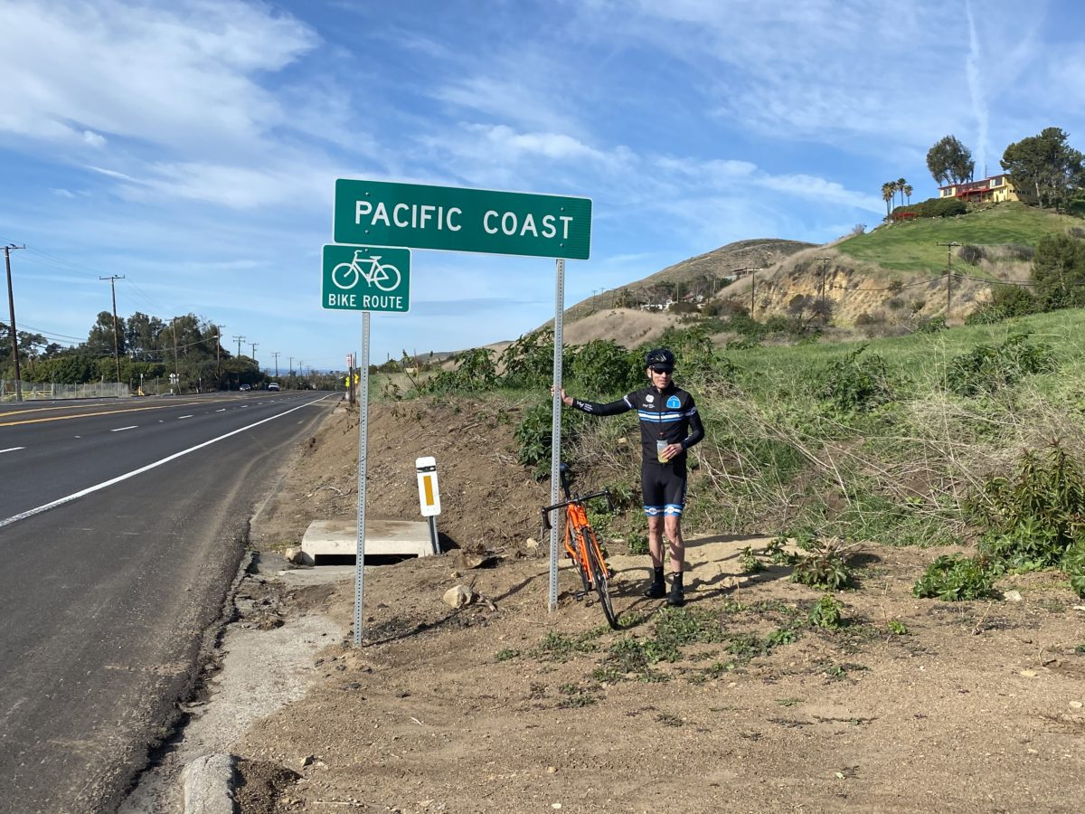 Coach Mike Neill standing next to Pacific Coast Highway sign at Vertical Camp